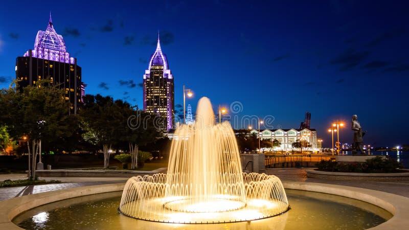 In die Stadt Mobile, Alabama-Skyline u. Wasser-Brunnen nachts stockbild