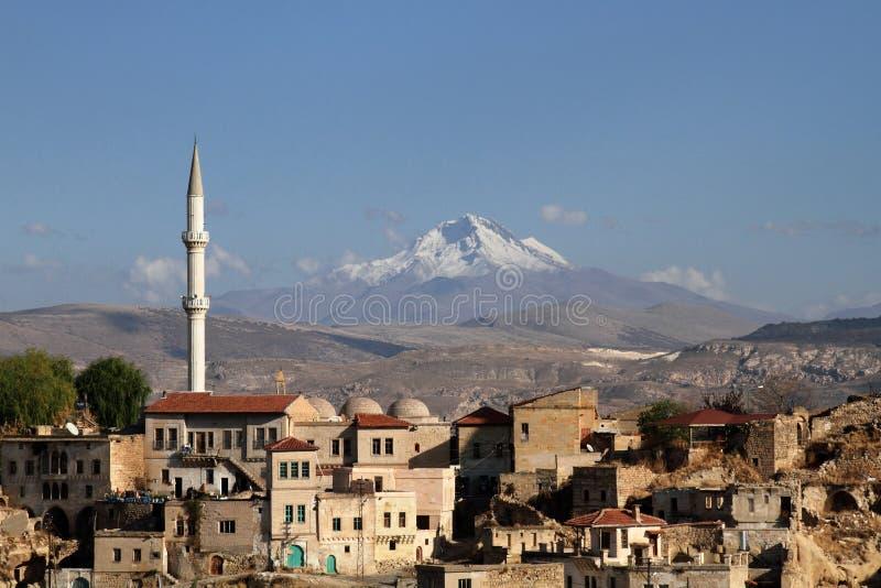 Die Stadt von Ortahisar in Cappadocia mit Berg Erciyes im Hintergrund lizenzfreies stockbild