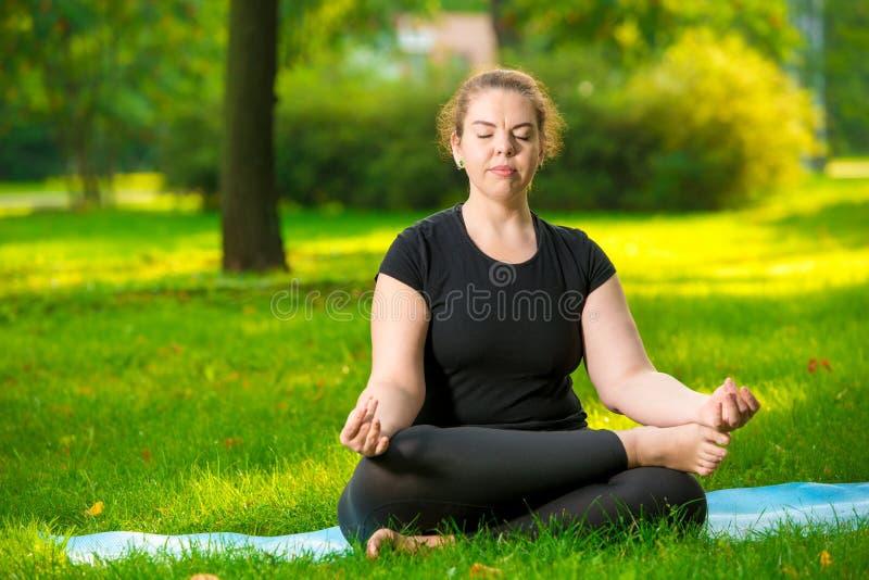 Die starke Überformat Frau meditiert auf dem Rasen im Park im Lotos stockbilder