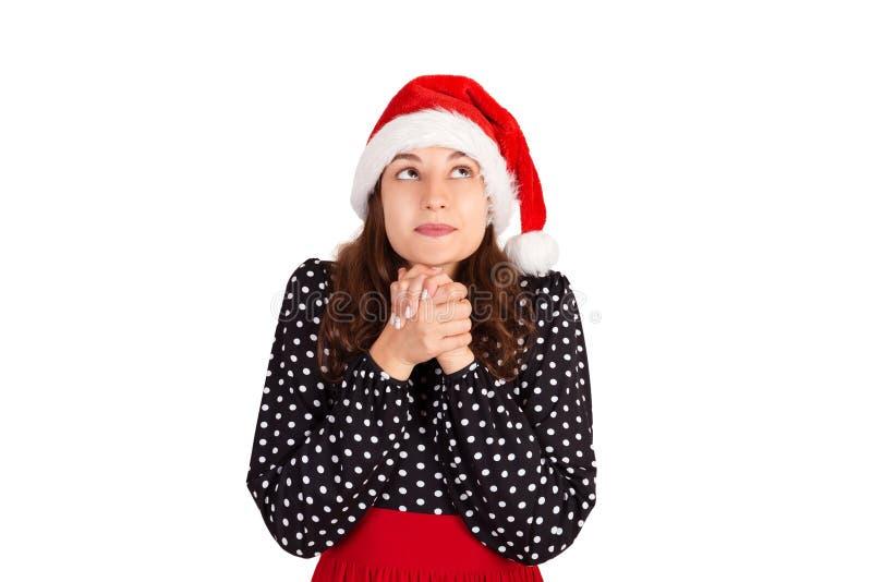 Die starke Frau im Kleid betend mit beten Geste und oben schauen emotionales Mädchen im Weihnachtsmann-Weihnachtshut lokalisiert  lizenzfreie stockfotos