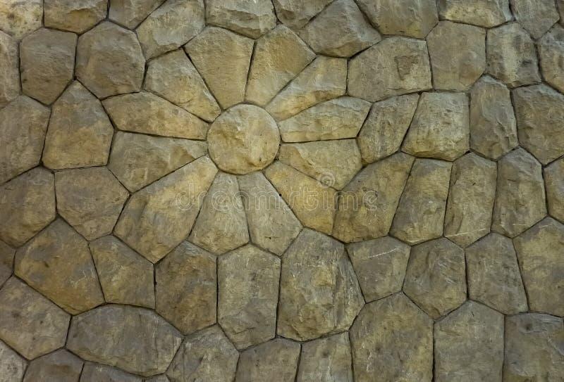 Die Steine, die in der Wand eingeschlossen sind, machen die Form von einer Blume und zeigen die Kunstfertigkeit und die künstleri stockfotos