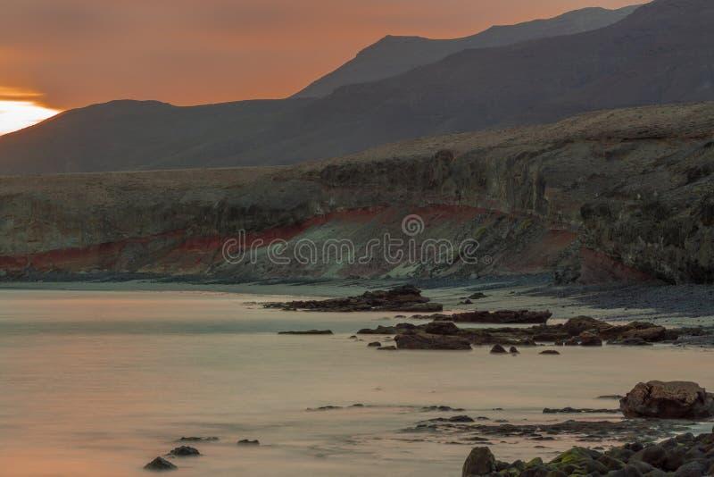 Die steinige Küste von Fürteventura bei Sonnenuntergang - lange Belichtung lizenzfreie stockbilder