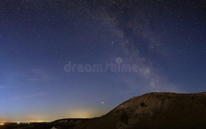 Die Sterne der Milchstraße im nächtlichen Himmel über einer hügeligen Landschaft stockbilder