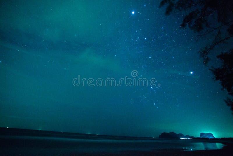 Die Sterne im bewölkten nächtlichen Himmel in dem Meer in Thailand lizenzfreies stockfoto