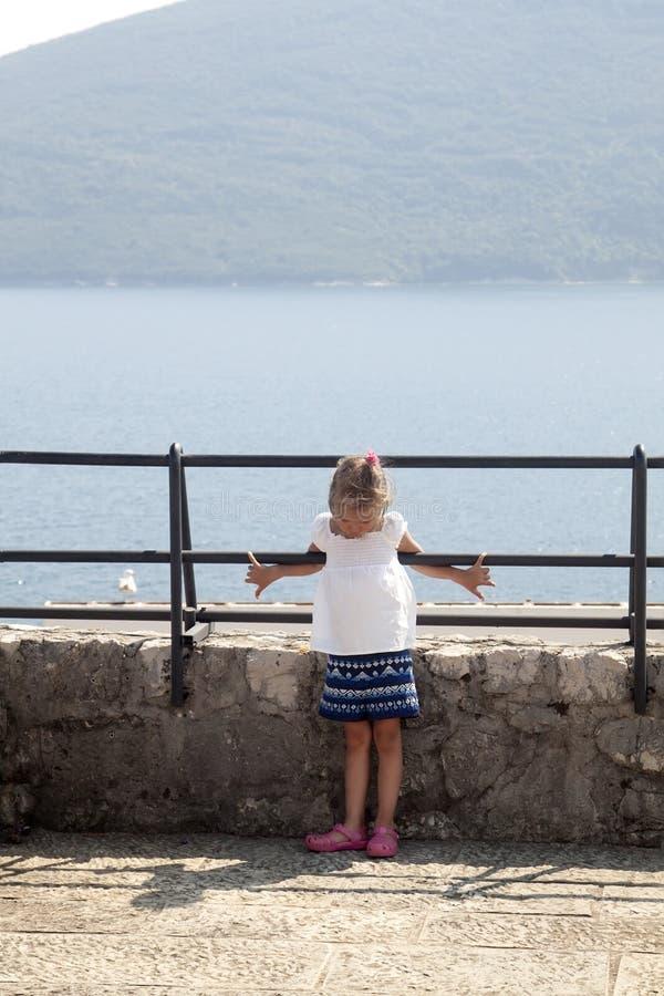 die Stirn gerunzeltes Mädchen wird auf der Aussichtsplattform mit einer atemberaubenden großartigen Ansicht der Boka-Kotorskabuch lizenzfreies stockfoto