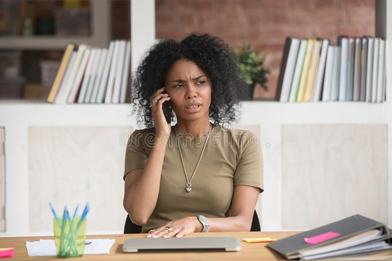Die Stirn runzelnde afrikanische Geschäftsfrau, die unangenehmes Gespräch am Telefon hat stockfoto