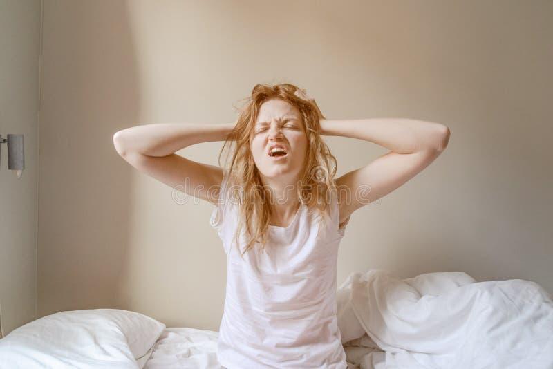 Die Stirn runzelnde Blondine im Bett mit den Händen auf Gesicht lizenzfreie stockbilder