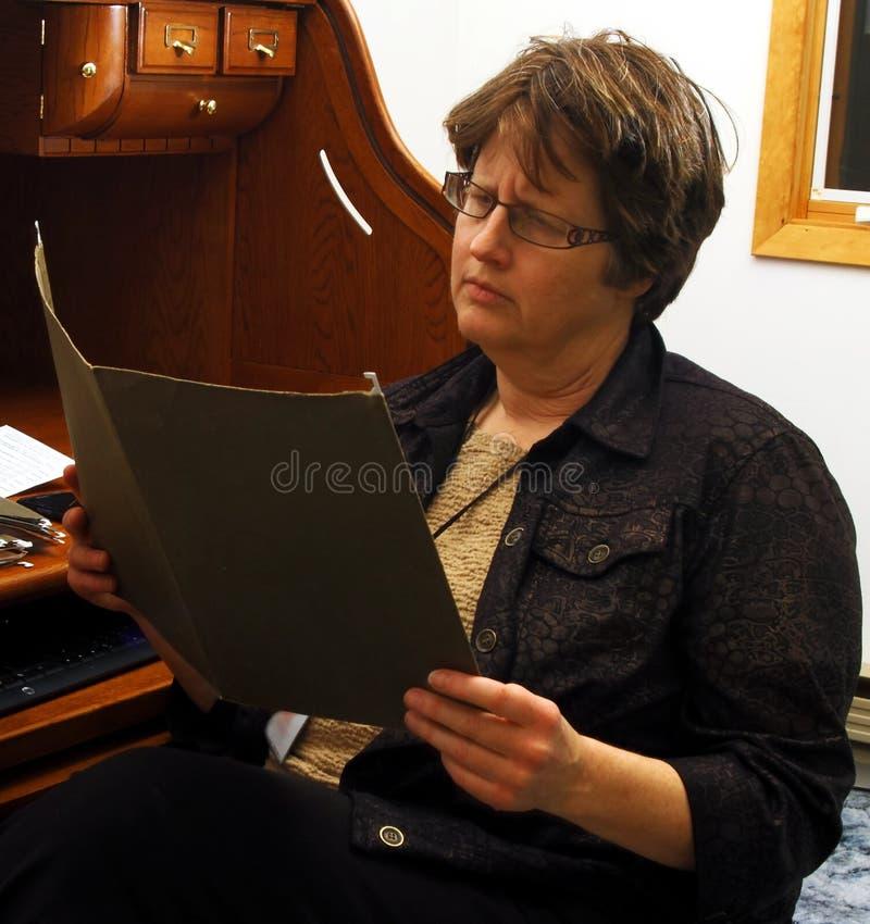 Die Stirn runzelnde Frau, die Papiere im Ordner betrachtet lizenzfreies stockbild
