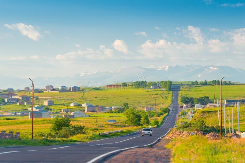 Die Straße, das armenische Dorf und die Ansicht der schneebedeckten Spitzen der Berge von Armenien auf einem Sommer lizenzfreie stockbilder