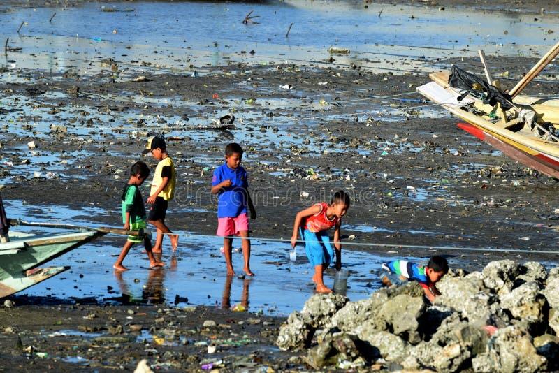 Die suchenden Muscheln der Kinder nahe Suramadu lizenzfreie stockbilder