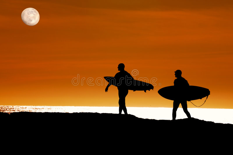 Die Surfer, die zum Ozean für einen Sonnenuntergang gehen, reiten stockbilder