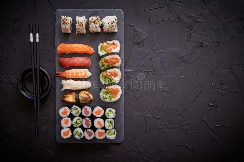 Die Sushirollen, die mit Lachsen und Thunfischen eingestellt wurden, dienten auf schwarzem Steinbrett lizenzfreies stockbild