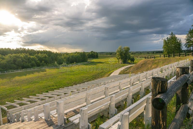 Die Symmetrie der weißen Bänke im Stadion im Wald gelegen auf dem Hintergrund von Sturmwolken stockfotos