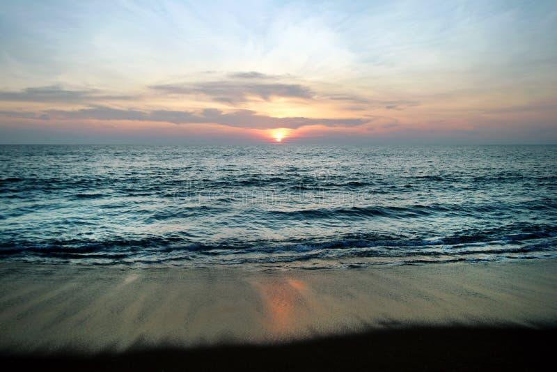 Die szenische Ansicht über ein Meer und der Sand setzen mit buntem Sonnenuntergang auf den Strand stockfotos