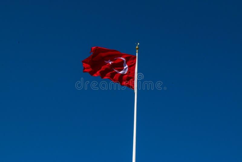 Die Türkei-Flagge mit Hintergrund des blauen Himmels lizenzfreies stockfoto