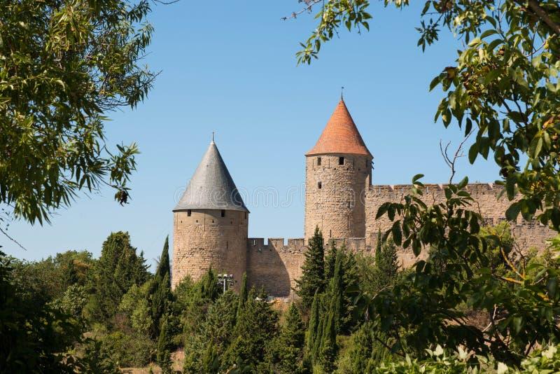 Die Türme von Carcassonne-Zitadelle gestaltet durch Bäume an einem sonnigen Tag stockfotos