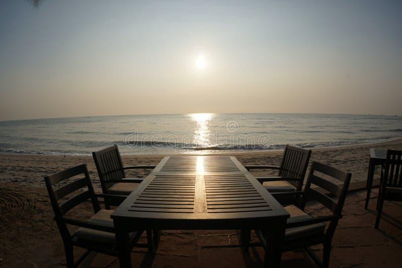 Die Tabelle des Abendessens bei Sonnenuntergang oder des Sonnenaufgangs auf dem Strand lizenzfreies stockbild