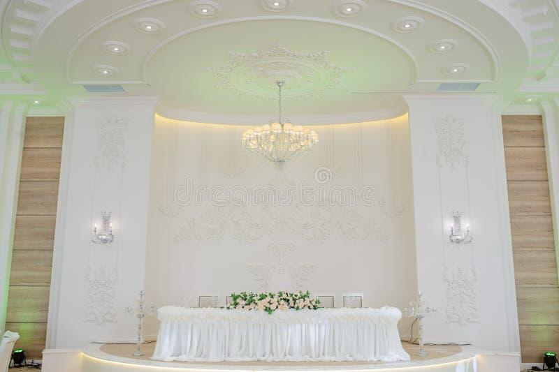 Die Tabelle verziert mit Blumen und einem Leuchter in einer Banketthalle lizenzfreie stockbilder