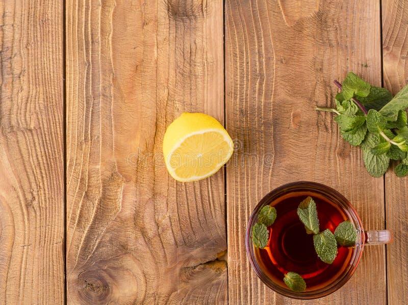Die Tasse Tee mit Minze und Zitrone auf braunem Holztisch stockfotografie
