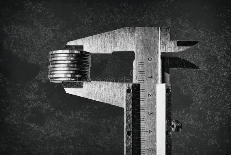 Die Tasterzirkel, die Münzenfinanzeinkommen messen, profitieren Nahaufnahme auf dem dunklen Hintergrund stockfoto