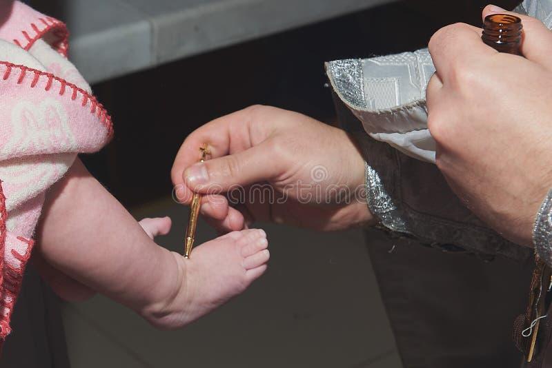 Die Taufe eines Kindes der Priester tut das Salben lizenzfreie stockbilder