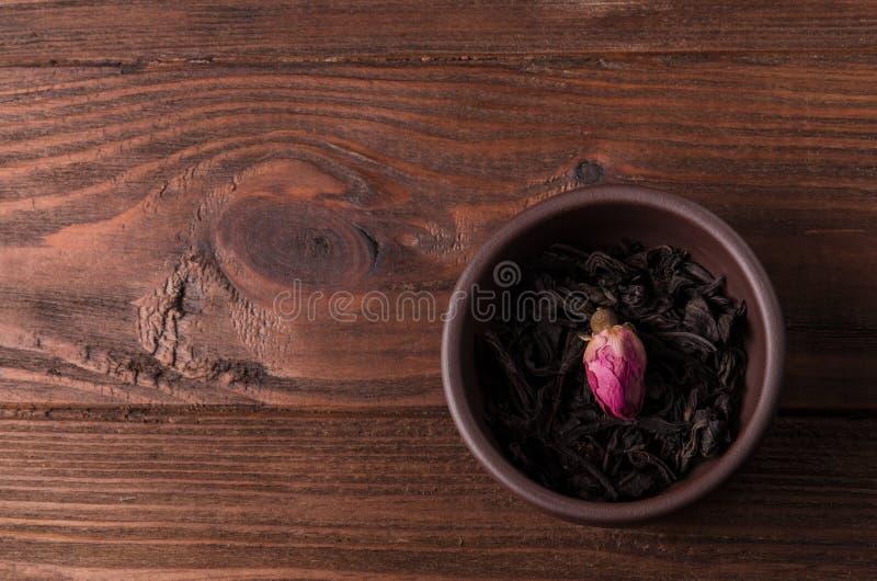 Die Teeschale, mit lose getrocknete schwarze Teeblätter und eine rosafarbene Knospe des Tees, ist auf dem Holztisch lizenzfreies stockfoto