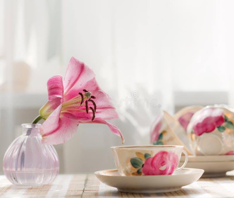 Die Teeschale wird mit freundlich rosa Blumen verziert lizenzfreies stockfoto