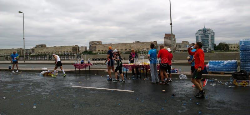 Die Teilnehmer des Marathon ` weiße Nacht-` bei einem der Nahrungsmittel in der Mitte von Petersburg lizenzfreie stockfotos