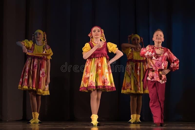 Die Theatervorstellung der Kinder der Tanzgruppe in den nationalen Kostümen lizenzfreie stockbilder