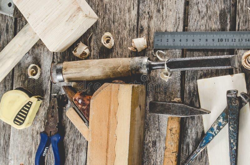 Die Tischlerwerkzeuge auf Holzbank, Fläche, Meißel, Holzhammer, Maßband, Hammer, Zangen, Zangen, Niveau, Nägeln und einer Säge stockfotos
