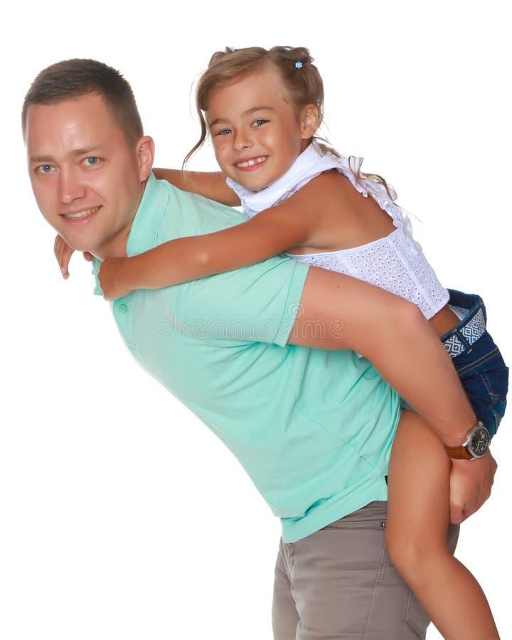 Die Tochter fährt auf Papa ` s Schultern lizenzfreie stockfotografie