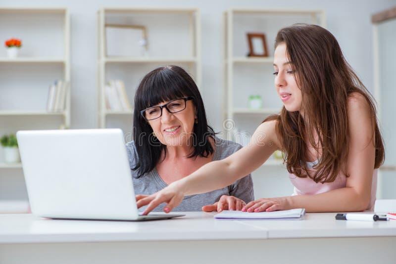 Die Tochter, die Mutter erklärt, wie man Computer benutzt stockfoto
