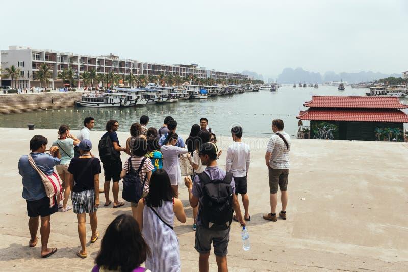 Die Touristen, die auf ein Boot zu Halong warten, bellen mit Kalksteininseln im Hintergrund im Sommer bei Quang Ninh, Vietnam stockfotografie
