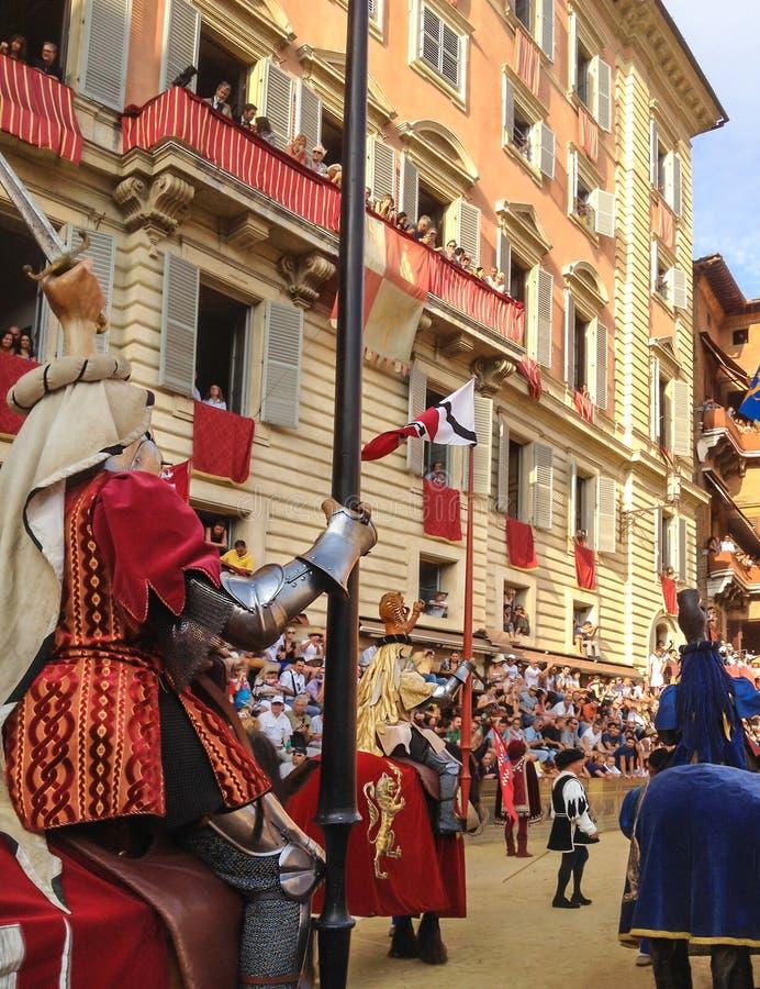 Die Touristen, die das bunte und fantastische traditionelle Kostüm aufpassen, führt am Pferderennen, Palio-Di Siena vor, gehalten stockfotos