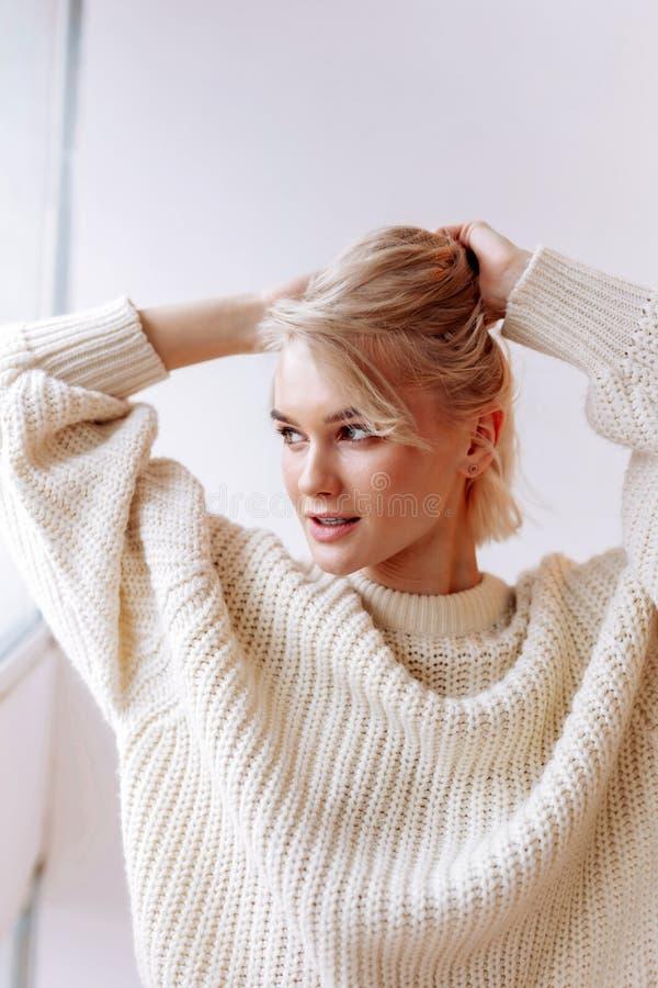 Die tragende Strickjacke der Frau appellieren, die morgens ihr Haar repariert lizenzfreie stockfotos