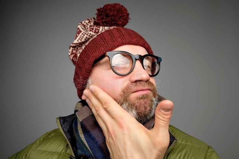Die tragenden Gläser des lustigen reifen Mannes und warme Kleidung, welche die Kamera überprüft seins betrachtet, empört sich stockfoto