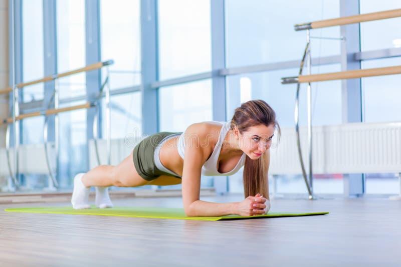Die Trainingseignungsfrau, welche die Plankenkernübung ausarbeitet für hintere Dorn und Lage Konzept pilates tut, tragen zur Scha lizenzfreie stockfotos