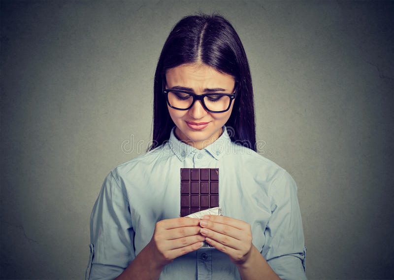 Die traurige Frau ermüdete von den Diätbeschränkungen BonbonSchokoriegel sehnend stockbilder