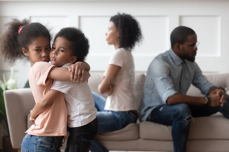 Die traurigen afrikanischen Kinder, die Umkippen an den Eltern umfassen, kämpfen zu Hause lizenzfreie stockbilder
