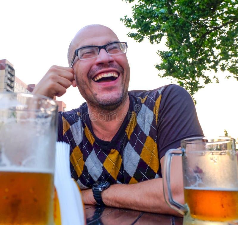 Die trinkenden Apfelweinwitze des Mannes, Lächeln Ein junger Mann trinkt Apfelwein in einem offenen Café und Blicke in den Abstan stockfoto