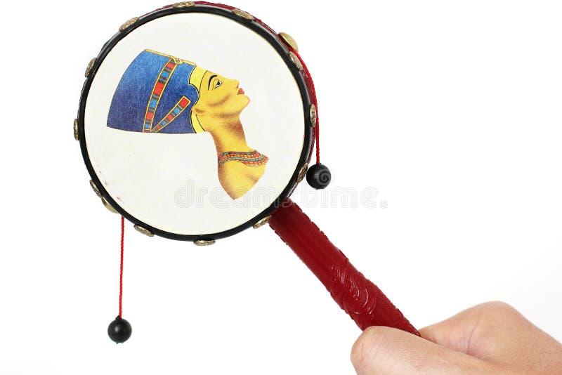 Die Trommel ist in der Hand Handtrommel mit Glocken auf einem weißen Hintergrund lizenzfreies stockfoto