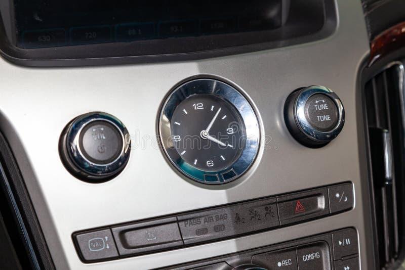 Die Uhr auf dem Armaturenbrett des Autos ist die Nahaufnahme, bedeckt mit natürlichem schwarzem Leder und Braun woooden Ordnung,  lizenzfreies stockbild