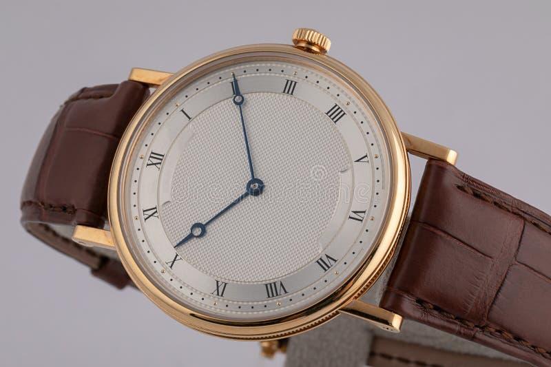 Die Uhr der Männer mit braunem Lederband, weiße Skala, im goldenen Körper, blaue rechtsläufige, schwarze Ziffern lokalisiert auf  stockfotografie