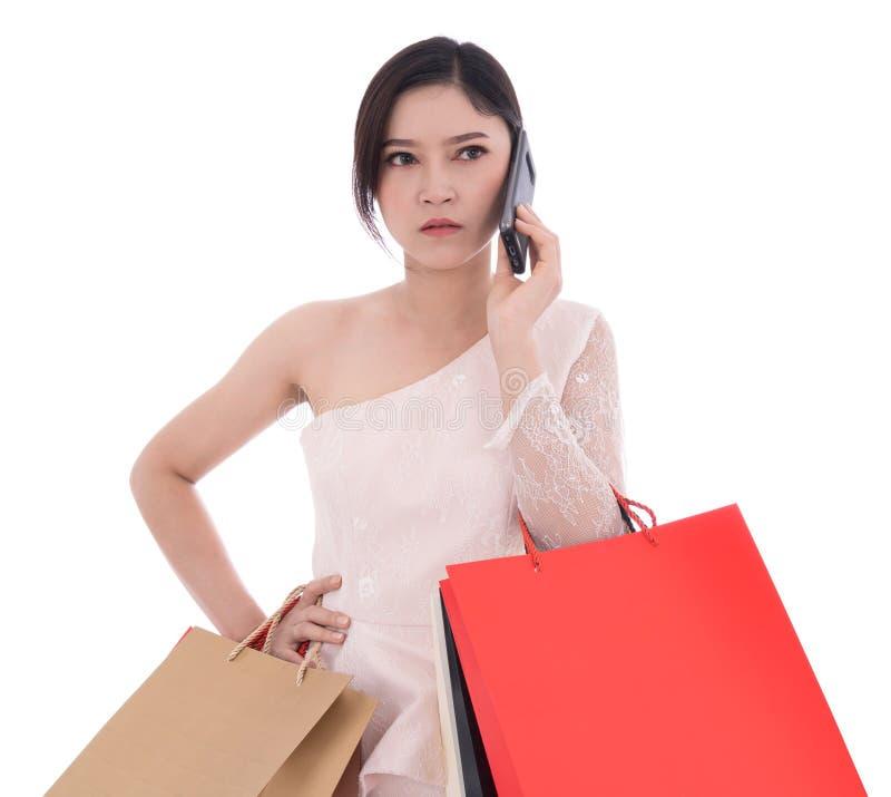 Die unglückliche Frau, die auf Smartphone spricht und Einkaufstaschen hält, ist lizenzfreie stockfotos