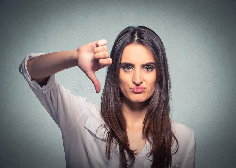Die unglückliche Frau, die Daumen gestikulieren gibt unten, das Schauen mit negativem Ausdruck stockfoto