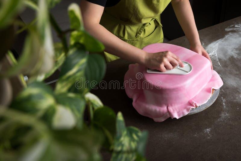 Die Unrecognisable Frau in der Bäckerei Herz verzierend formte Hochzeitstorte mit rosa Fondant lizenzfreies stockbild