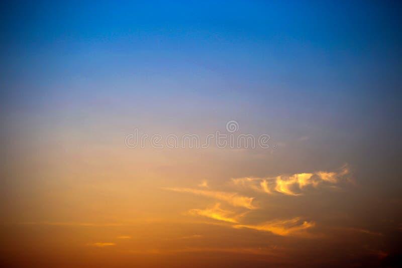 Die untergehende Sonne ist nahe, ist der blaue Himmel nahe, und die Wolken brennen im Abstand lizenzfreie stockfotos