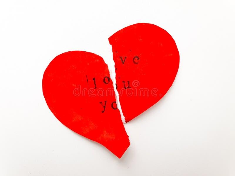 Die Valentinstaggrußkarte, die zur Hälfte in Form eines roten Herzens mit den Wörtern zerrissen wird, lieben Sie lizenzfreie stockbilder