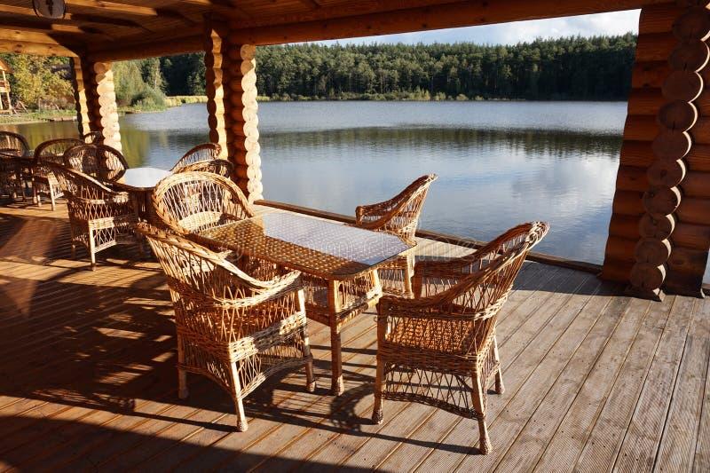 Die Veranda eines Holzhauses, auf dem es eine Tabelle und Stühle für die Entspannung gibt lizenzfreie stockfotos