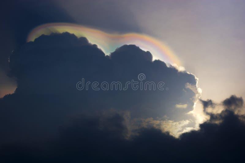 Die verbogenen Regenbogen, die unter Wolken und Sonne gesehen werden, erweitern sich stockfotos